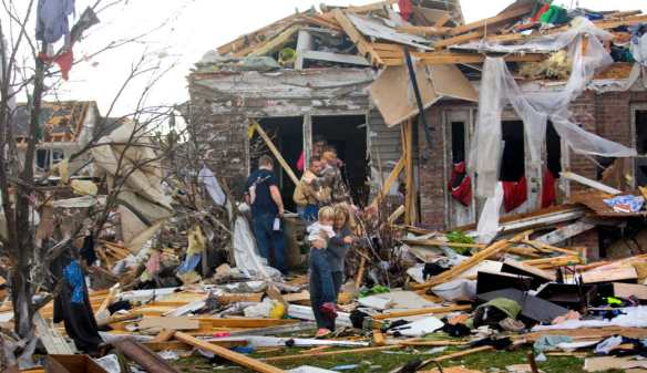 MATT DAYHOFF/JOURNAL STAR  Washington residents emerge from a damaged home in the Devonshire subdivision Sunday after a tornado stuck the town on Nov. 17.