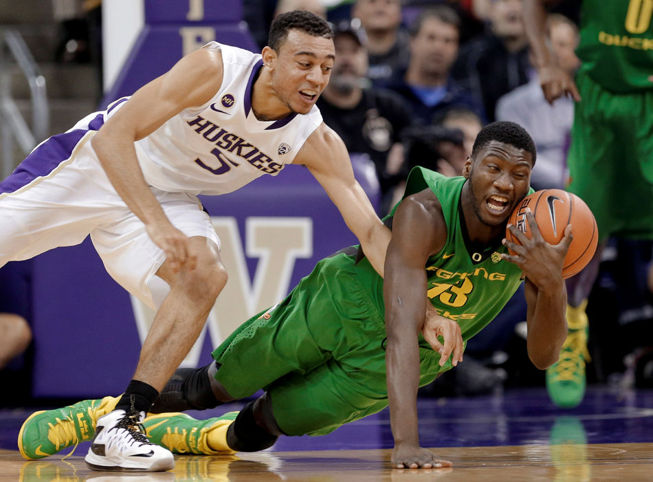 Washington's Nigel Williams-Goss, left, and Oregon's Richard Amardi dive for a loose ball during the first half of an NCAA college basketball game Thursday, Jan. 23, 2014, in Seattle. (AP Photo/Elaine Thompson)