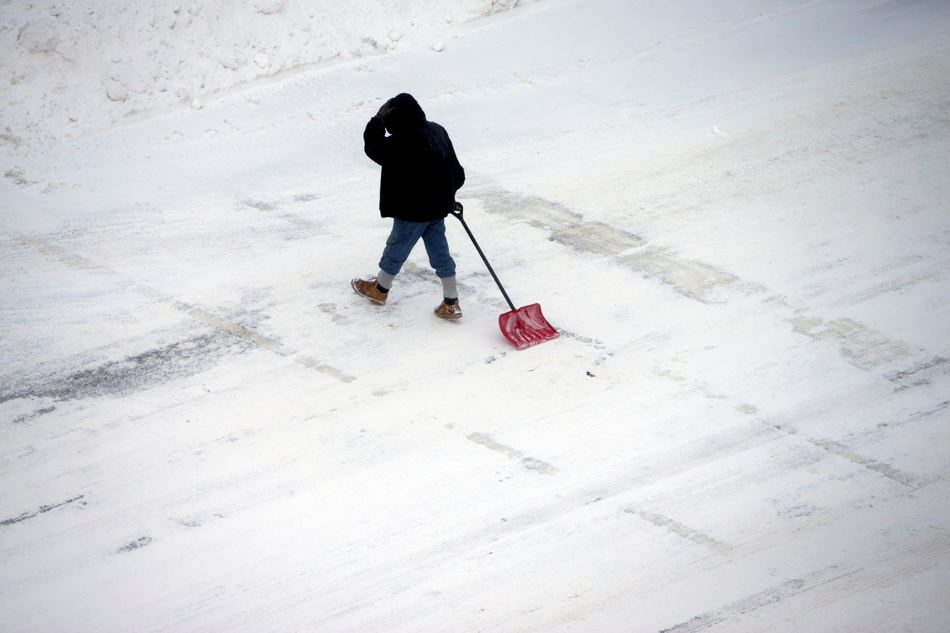 A pedestrian drags a shovel across Indiana 933 along Colfax Avenue on Monday, Jan. 27, 2014, in downtown South Bend. Sub-freezing temperatures and blowing snow returned to the Michiana area yet again as the City of South Bend declared a winter weather emergency. (AP Photo/South Bend Tribune, James Brosher)