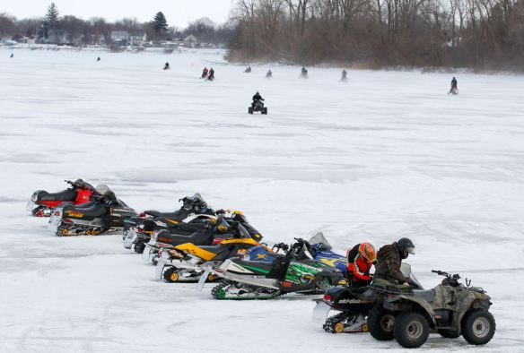 ROVRiders head in and out of the Oarhouse Bar and Grill on the Ottawa River during the Ottawa River Yacht Club's annual Winterfest poker run, Saturday, Jan. 25, 2014.  The bar was the third of five stops on the event.  (AP Photo/The Blade, Andy Morrison)