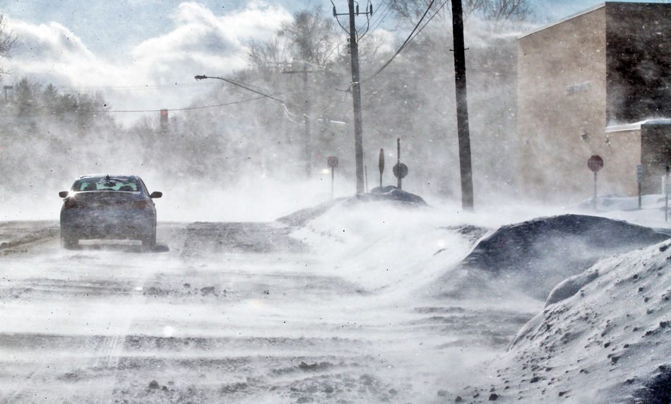 A strong westerly wind kicked up snow Sunday Jan. 26, 2014, drifting it over area roads and parking lots.  Snow drifted across Centerville Road in Vadnais Heights, Minn.  (AP Photo/The Star Tribune, Marlin Levison)