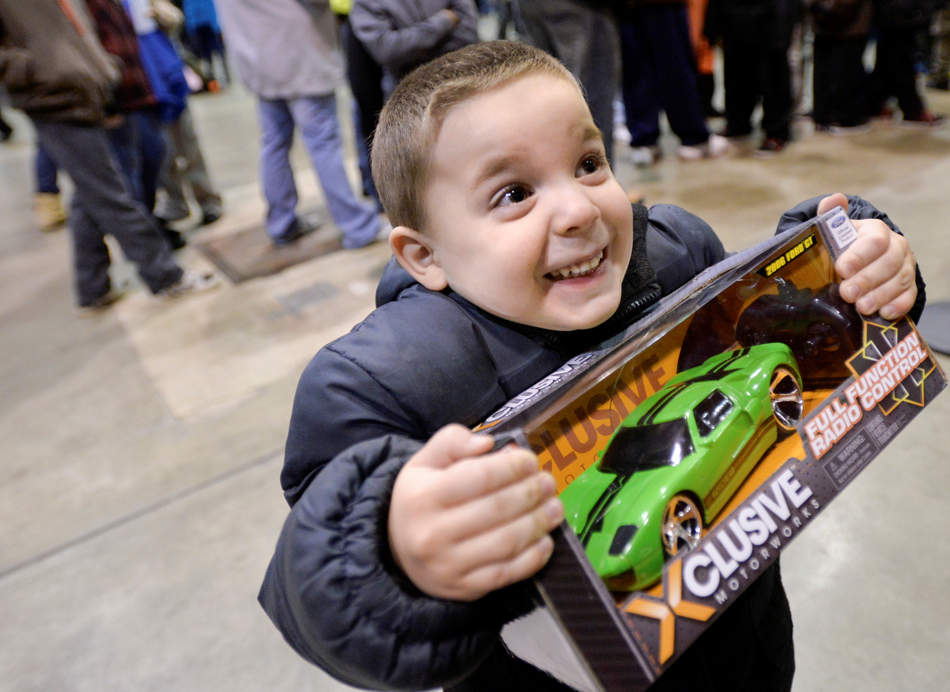 RON JOHNSON/JOURNAL STAR  Leo Allen, 4, of Peoria is excited to get a new toy for Christmas during the Salvation Army's Share the Spirit Party on Dec. 10 at the Peoria Civic Center. About 1,000 kids got to visit with Santa, have pizza,  and enjoy a new toy during the event.