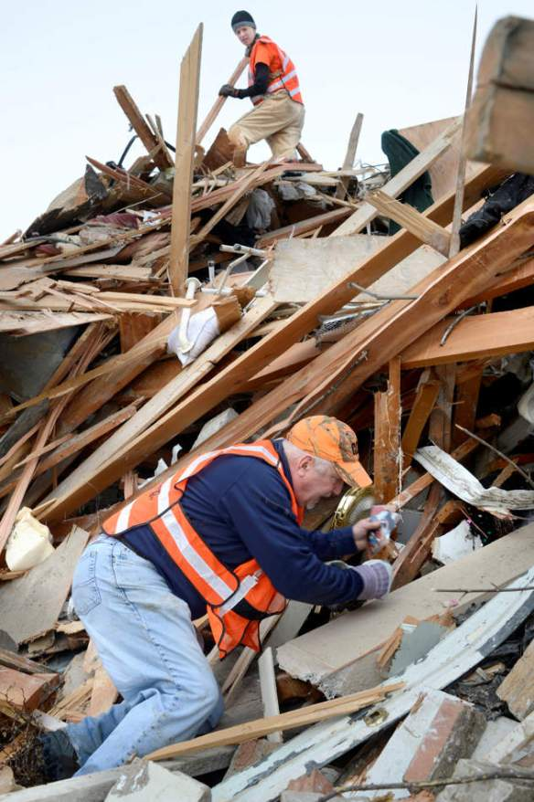 DAVID ZALAZNIK/JOURNAL STAR  Volunteer Jim Gleason pulls photographs to save from a pile of rubble as Michelle Holdham works at the crest of the pile on Dec. 19 in Washington.