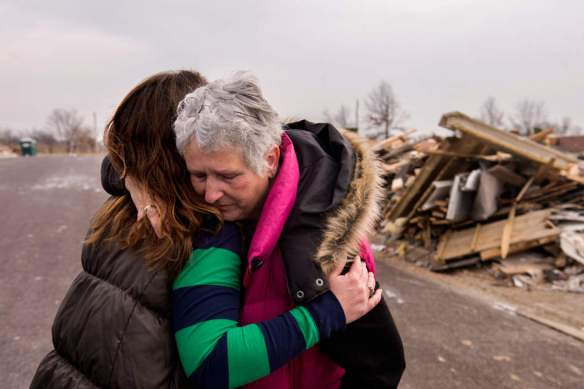 "FRED ZWICKY/JOURNAL STAR When the tornado ripped through Washington, Pat Conner, right, was in her bedroom, bent over letting her dog out of his dog crate. Pat was picked up by the tornado and spun around five times, landing outside the house. Weeks after the storm on Dec. 2, Pat embraces her neighbor Rachel Wilkins, seeing her for the first time after the disaster. Pat said, ""The only thing I remember thinking is 'You're going to die."" Pat survived with injuries, but her home was destroyed."