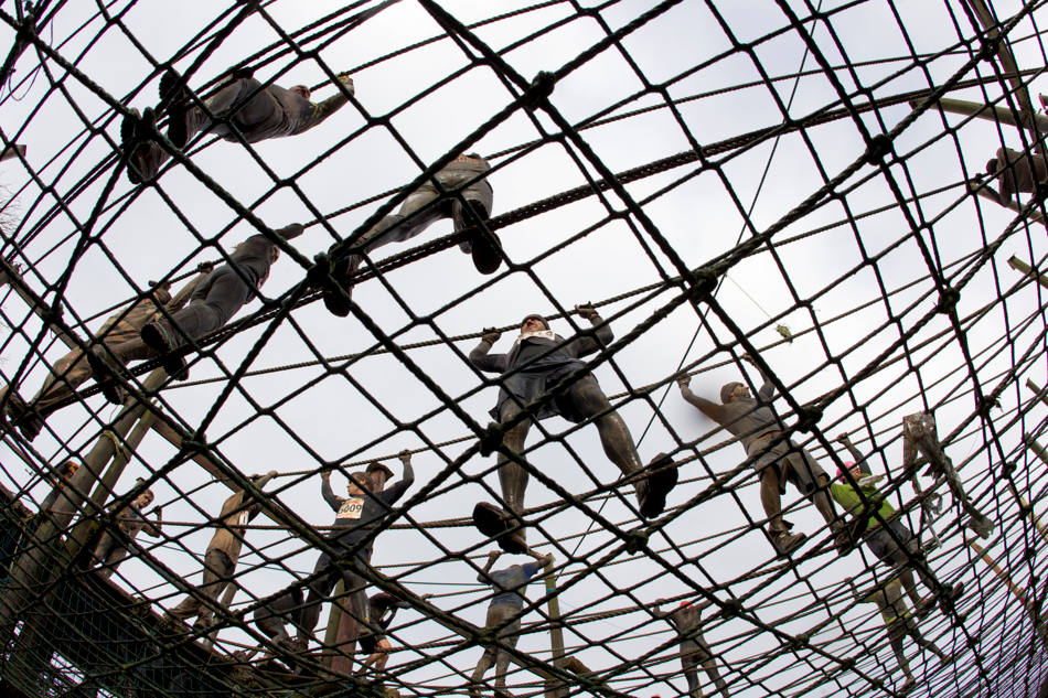 "Competitors makes their way across an obstacle during the annual Tough Guy race ""the toughest race in the world"" at Perton in Staffordshire, England, Sunday Jan. 26, 2014. Tough Guy claims to be the world's most demanding one-day survival ordeal. First staged in 1987, the Tough Guy Challenge has been widely described as one of the hardest races of it's type with up to one-third of the starters failing to finish in a typical year. (AP Photo/Jon Super)"