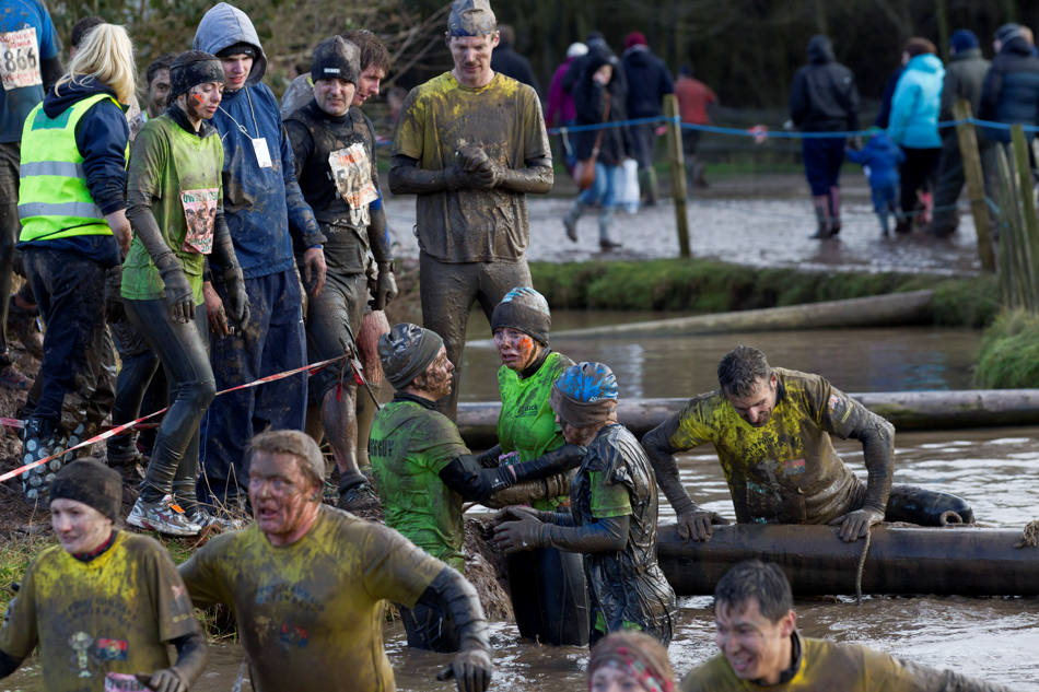 "A competitor, right, struggles with an obstacle during the annual Tough Guy race ""the toughest race in the world"" at Perton in Staffordshire, England, Sunday Jan. 26, 2014. Tough Guy claims to be the world's most demanding one-day survival ordeal. First staged in 1987, the Tough Guy Challenge has been widely described as one of the hardest races of it's type with up to one-third of the starters failing to finish in a typical year. (AP Photo/Jon Super)"