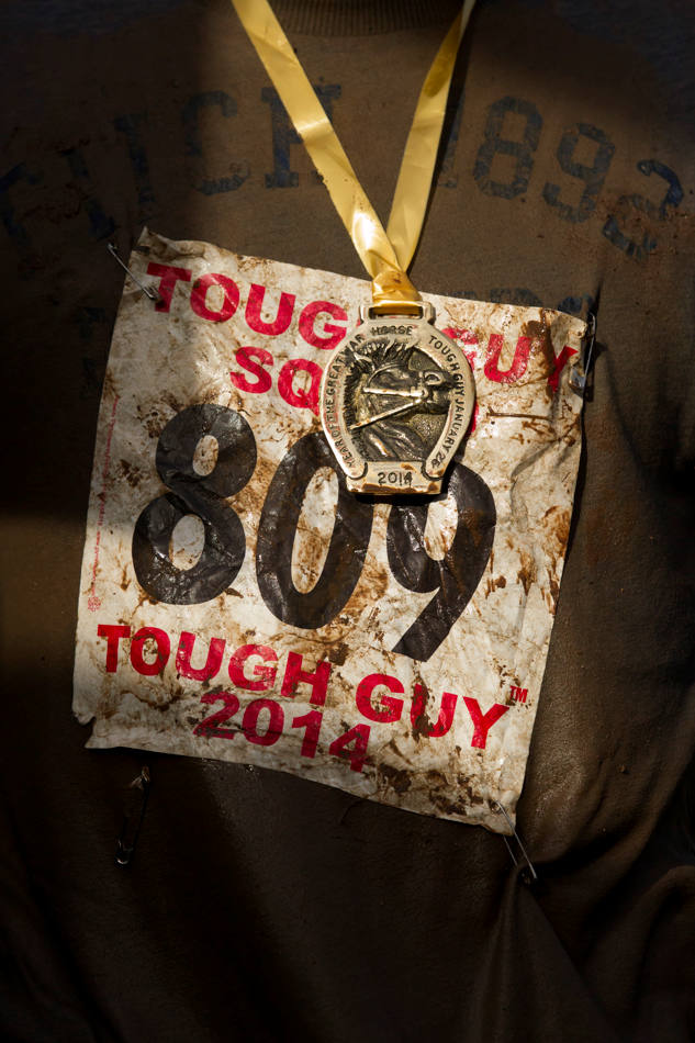 "A finishers medal is seen on a competitors race number after the annual Tough Guy race ""the toughest race in the world"" at Perton in Staffordshire, England, Sunday Jan. 26, 2014. Tough Guy claims to be the world's most demanding one-day survival ordeal. First staged in 1987, the Tough Guy Challenge has been widely described as one of the hardest races of it's type with up to one-third of the starters failing to finish in a typical year. (AP Photo/Jon Super)"