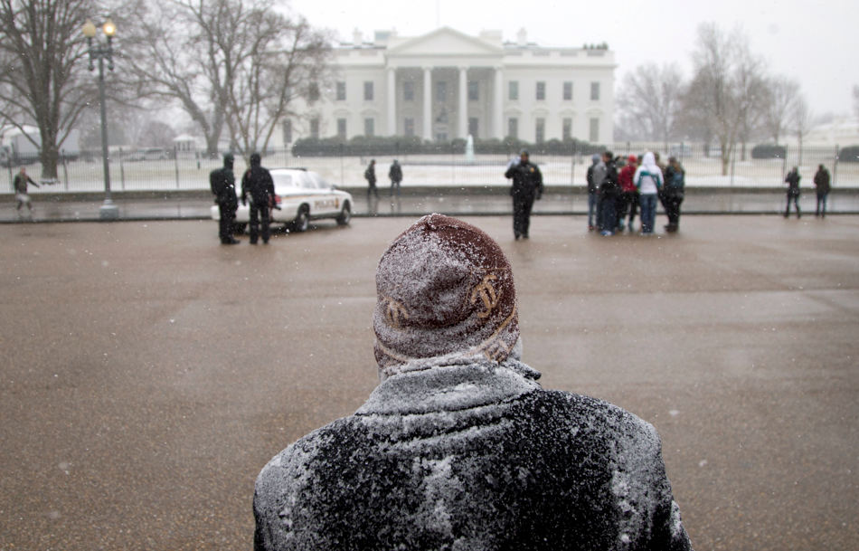 Snow accumulates at the shoulders and head of Ramond Salcedo from the Dominican Republic, as he stands outside the White House, Tuesday, Jan. 21, 2014, Washington. Many Washington offices and area schools closed before the first flake of snow fell from the sky, but there are signs that significant winter weather is moving in. (AP Photo/Carolyn Kaster)