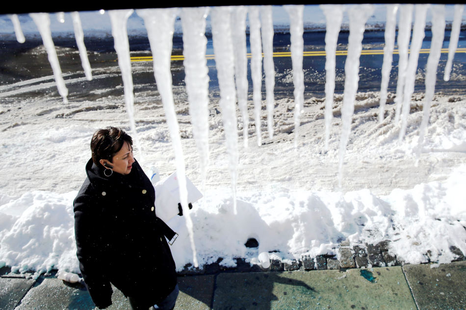 A women walks past icicles hanging from a store awning Wednesday, Jan. 22, 2014, in Philadelphia.  A winter storm stretched from Kentucky to New England and hit hardest along the heavily populated Interstate 95 corridor between Philadelphia and Boston.   (AP Photo/Matt Rourke)