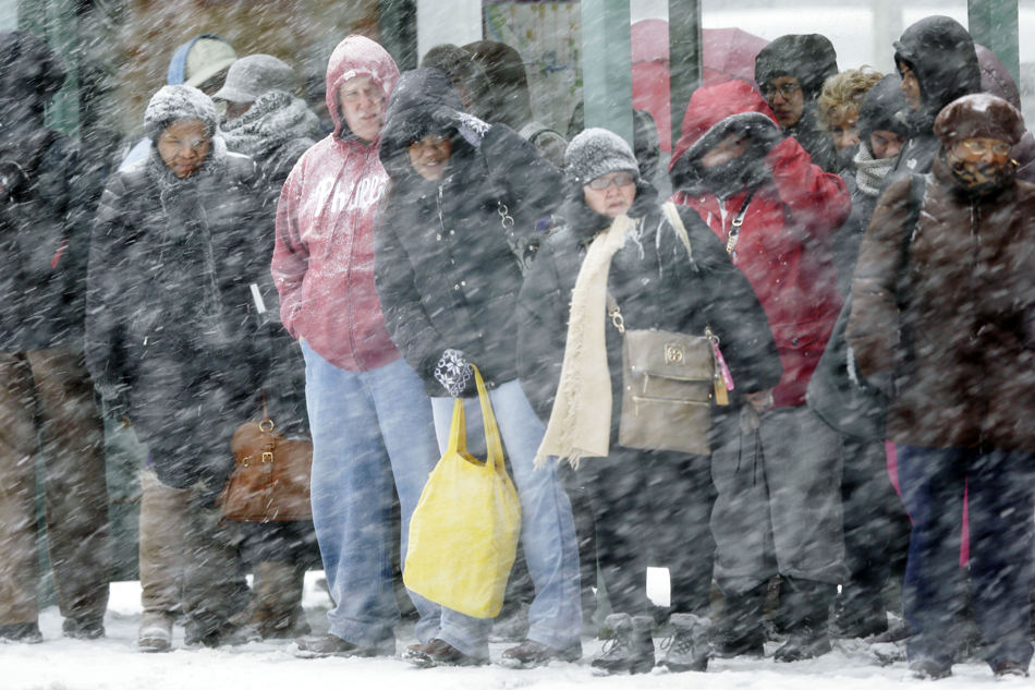Commuters wait for a bus during a winter snowstorm Tuesday, Jan. 21, 2014, in Philadelphia. A storm is sweeping across the Mid-Atlantic and New England. The National Weather Service said the storm could bring 8 to 12 inches of snow to Philadelphia and New York City, and more than a foot in Boston.  (AP Photo/Matt Rourke)