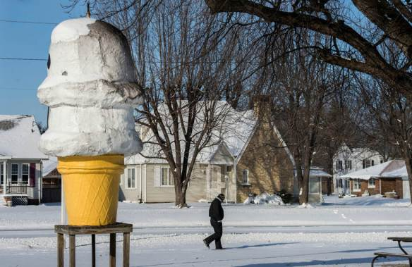 FRED ZWICKY/JOURNAL STAR  A giant ice cream cone beckons outside a closed-for-the-season Double D's Ice Cream in Pekin as Kevin Weaver walks to scout the main roads on January 6 to see if he can make it to work.