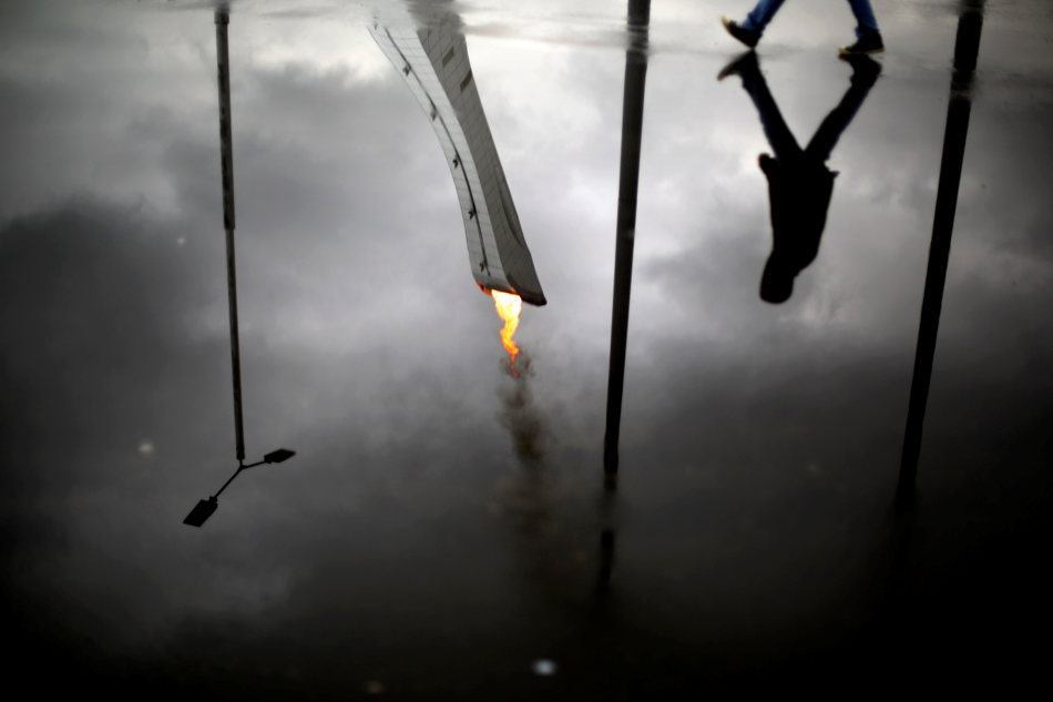 The Olympic flame is reflected in a puddle while lit during a test in the Olympic Park for the upcoming 2014 Winter Olympics as a pedestrian passes by, Friday, Jan. 31, 2014, in Sochi, Russia. (AP Photo/David Goldman)