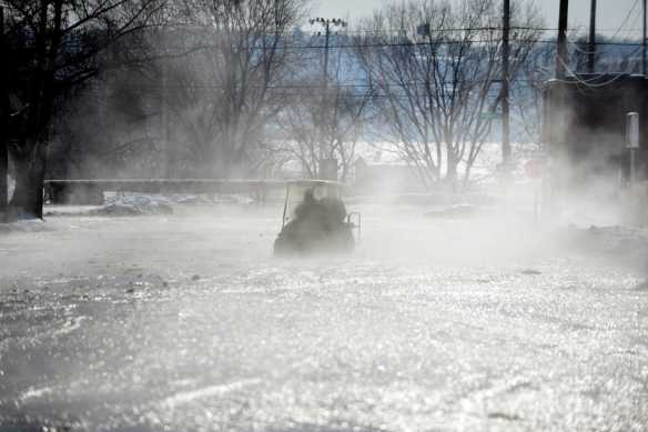 DAVID ZALAZNIK/JOURNAL STAR  Two men steer a golf cart through steam rising from water pouring down Abington St. to Adams St. after a water main break at Jefferson Ave. and Abington St. on Monday, Feb. 10.