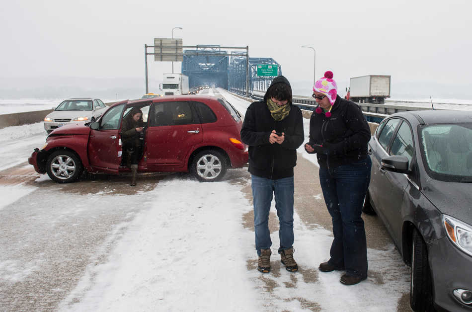 FRED ZWICKY/JOURNAL STAR Drivers exchange information after a multi-car accident on the McClugage bridge shut down all but one lane of traffic Monday, Feb.17.