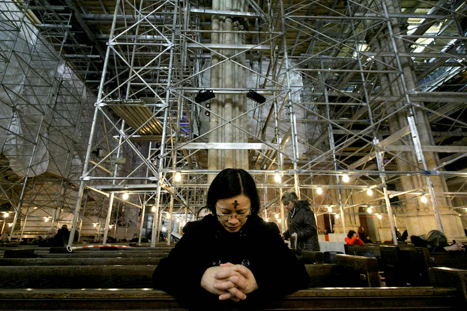 A woman prays at St. Patrick's Cathedral, Wednesday, March 5, 2014 in New York. Some Protestant, and all Catholic churches, distribute ashes on the forehead as a sign of repentance and renewal on Ash Wednesday as the 40-day season leading to Easter begins. The cathedral is filled with scaffolding as it is undergoing renovations. (AP Photo/Mark Lennihan)
