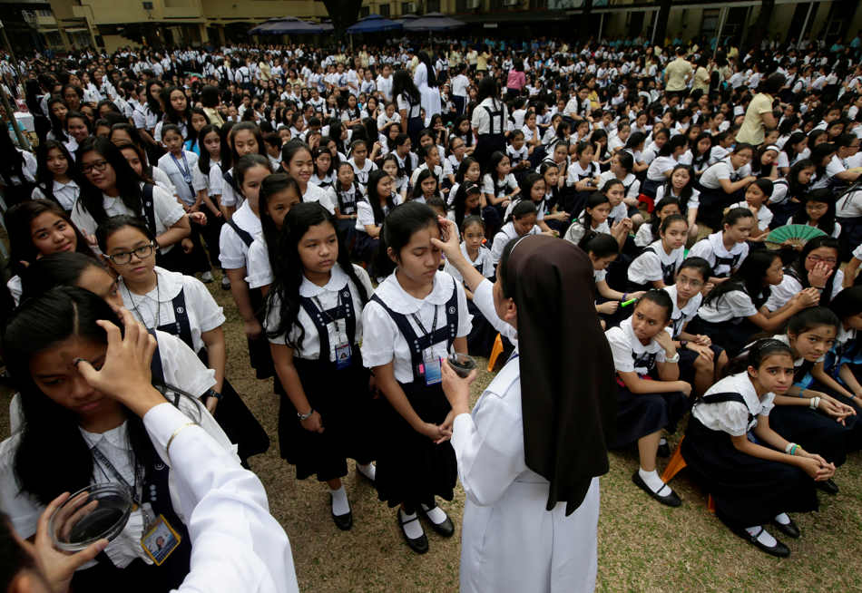 A Roman Catholic priest and a nun make a sign of the cross on the foreheads of students using ashes from burnt palms from last year in observance of Ash Wednesday to usher the 40-day Season of Lent Wednesday, March 5, 2014 at Saint Scholastica's College, a Catholic school in Manila, Philippines. The Ash Wednesday is observed among Catholics worldwide to urge people to repent and to remind mankind that they are mortals. (AP Photo/Bullit Marquez)