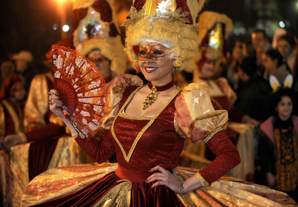 A woman in costume participates in a carnival procession in the southeastern Macedonia's town of Strumica, on Saturday, March 1, 2014. Some 2,500 disguised people participated on the main carnival evening. (AP Photo/Boris Grdanoski)