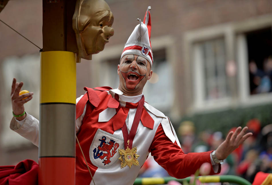 A reveller celebrates on a carnival float during the traditional carnival parade in Duesseldorf, western Germany, on Monday, March 3, 2014. The foolish street spectacles in the carnival centers of Duesseldorf, Mainz and Cologne, watched by hundreds of thousands of people, are the highlights in Germany's carnival season on Rose Monday. (AP Photo/Martin Meissner)