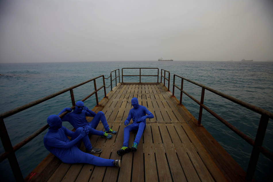 Men in the blue costumes are seen at a pier during the traditional parade to mark the end of the carnival period, in the southern port city of Limassol, southern of capital Nicosia, Cyprus, Sunday, March 2, 2014. Thousands of people gather every year to celebrate the Carnival in the streets.  (AP Photo/Petros Karadjias)