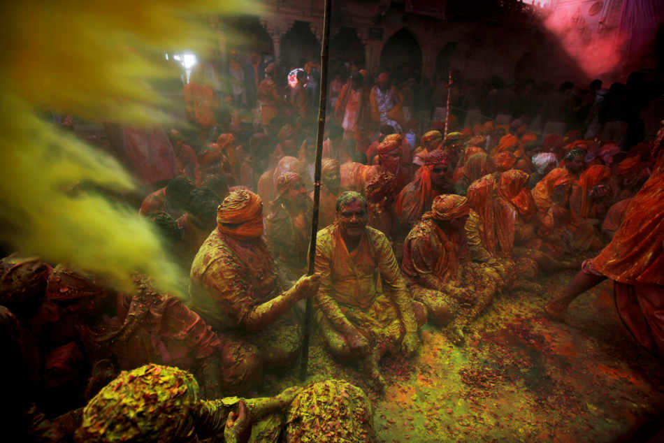 Hindu men from the village of Nangaon covered with colored powder sit on the floor during prayers at the Ladali or Radha temple before the procession for the Lathmar Holy festival, the legendary hometown of Radha, consort of Hindu God Krishna, in Barsana 115 kilometers ( 71 miles) from New Delhi, India, Sunday, March 9, 2014. During Lathmar Holi the women of Barsana beat the men from Nandgaon, the hometown of Krishna, with wooden sticks in response to their teasing as they depart the town. (AP Photo/Altaf Qadri)