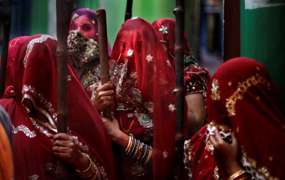 Indian women from Barsana village wait with a wooden sticks at the door step of their house for the arrival of villagers from Nandgaon, during the Lathmar Holy festival the legendary hometown of Radha, consort of Hindu God Krishna, in Barsana, 115 kilometers (71 miles) from New Delhi, India,Sunday, March 9, 2014. During Lathmar Holi the women of Barsana beat the men from Nandgaon, the hometown of Krishna, with wooden sticks in response to their teasing as they depart the town. (AP Photo/Altaf Qadri)