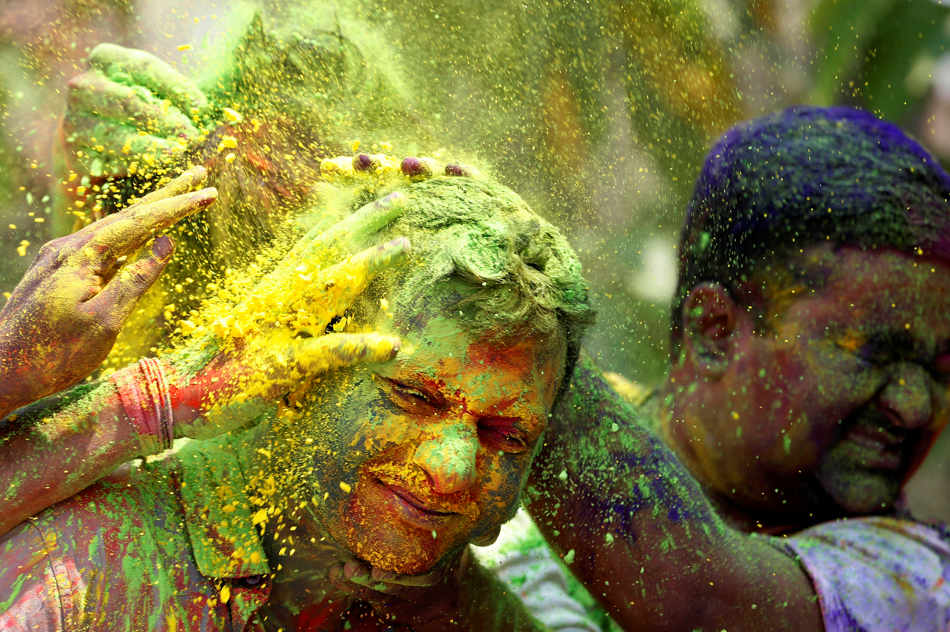 Indians smear colored powder at each other during celebrations marking Holi, the Hindu festival of colors, in Mumbai, India, Monday, March 17, 2014. The holiday, celebrated mainly in India and Nepal, marks the beginning of spring and the triumph of good over evil. (AP Photo/Rajanish Kakade)