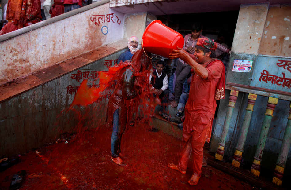 A Hindu man pours a bucket of colored water on a woman outside the Ladali or Radha temple before the procession for the Lathmar Holi festival, the legendary hometown of Radha, consort of Hindu God Krishna, in Barsana 115 kilometers ( 71 miles) from New Delhi, India, Sunday, March 9, 2014. During Lathmar Holi the women of Barsana beat the men from Nandgaon, the hometown of Krishna, with wooden sticks in response to their teasing as they depart the town. (AP Photo/Altaf Qadri)