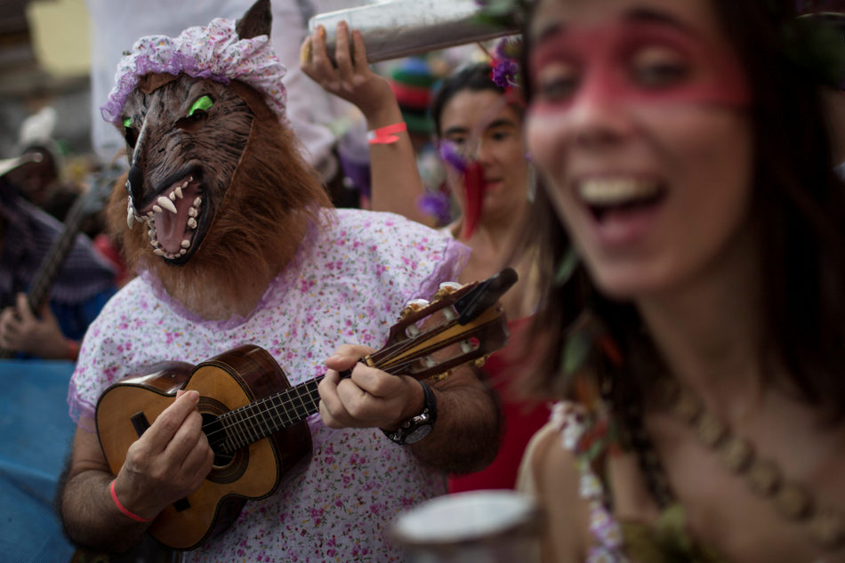 "Dressed as The Big Bad Wolf from the fairytale Little Red Riding Hood, a reveler strums a cavaquinho, a small four-stringed guitar, at the Heaven on Earth block party during Carnival celebration in Rio de Janeiro, Brazil, Saturday, March 1, 2014. Rio's over-the-top Carnival is the highlight of the year for many local residents. Hundreds of thousands of merrymakers will take to the streets in the nearly 500 open-air ""bloco"" parties. (AP Photo/Felipe Dana)"