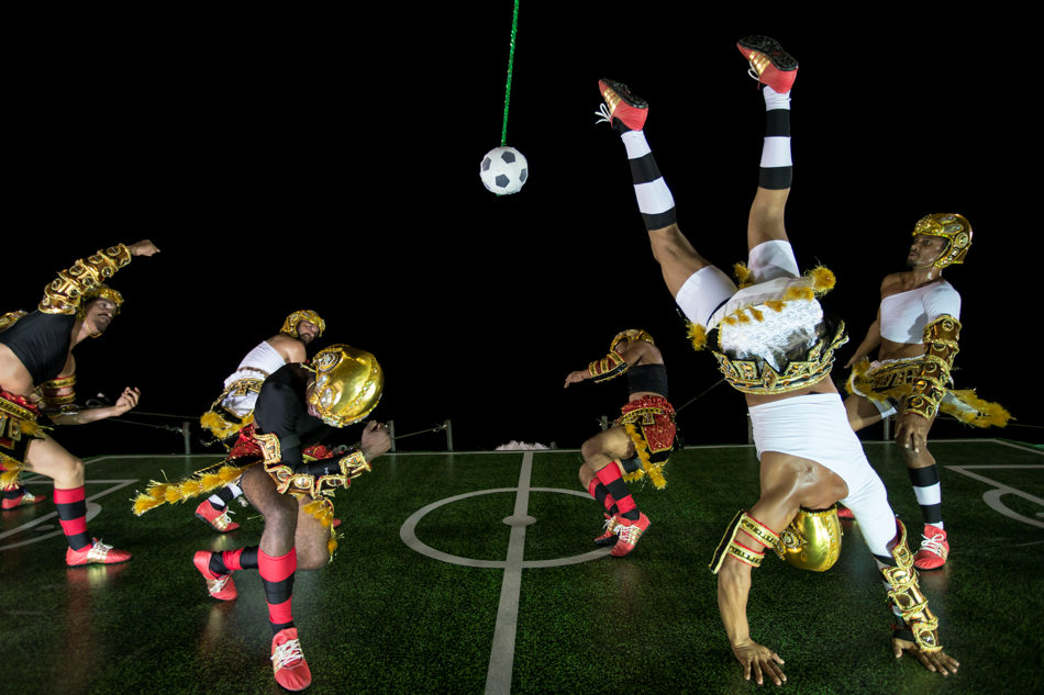 Performers from the Imperatriz Leopoldinense samba school pretend to play soccer as they hang on the wall of a float during carnival celebrations at the Sambadrome in Rio de Janeiro, Tuesday, March 4, 2014. (AP Photo/Felipe Dana)
