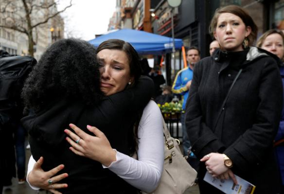 Olivia Savarino, center, hugs Christelle Pierre-Louis, left, as Callie Benjamin, right, looks on near the finish line of the Boston Marathon during ceremonies on Boylston Street, Tuesday, April 15, 2014, in Boston. Savarino and Benjamin were working at the Forum restaurant when a bomb went off in front of the building on April 15, 2013. (AP Photo/Steven Senne)