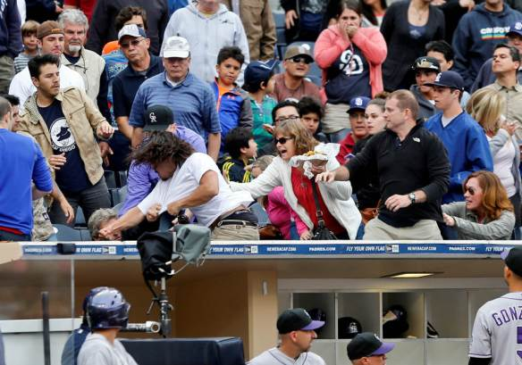 Colorado Rockies players come out of the dugout as fans throw punches during a fight in the stands that briefly delayed the Rockies' baseball game against the San Diego Padres during the seventh inning Thursday, April 17, 2014, in San Diego. (AP Photo/Lenny Ignelzi)