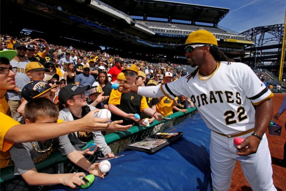 Pittsburgh Pirates' Andrew McCutchen (22) hands out autographed plastic easter eggs to youn fans before a baseball game against the Milwaukee Brewers in Pittsburgh Sunday, April 20, 2014. The Brewers won in 14 innings, 3-2. (AP Photo/Gene J. Puskar)