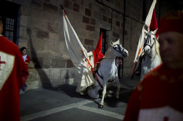 "A penitent falls together with the horse as they take part in the ""Procesion del Silencio"" by the ""Cristo de las Injurias"" brotherhood, during the Holy Week in Zamora, Spain, Wednesday, April 16, 2014. Hundreds of processions take place throughout Spain during the Easter Holy Week. (AP Photo/Andres Kudacki)"