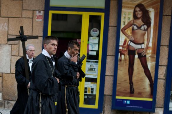 Penitents of the Jesus Nazareno brotherhood pass by a lingerie shop as they take part in a Holy Week procession in Zamora, northern Spain Friday, April 18, 2014. Hundreds of processions take place throughout Spain during the Easter Holy Week. (AP Photo/Andres Kudacki)