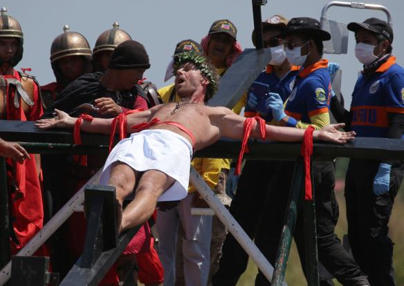 CORRECTS NAME OF THE VILLAGE - Danish national Lasse Spang Olsen, a 48-year-old filmmaker, grimaces as he is nailed to a cross to re-enact the crucifixion of Jesus Christ in San Pedro Cutud village, Pampanga province, northern Philippines on Friday, April 18, 2014. Church leaders and health officials have spoken against the practice which mixes Roman Catholic devotion with folk belief, but the annual rites continue to draw participants and huge crowds. (AP Photo/Aaron Favila)