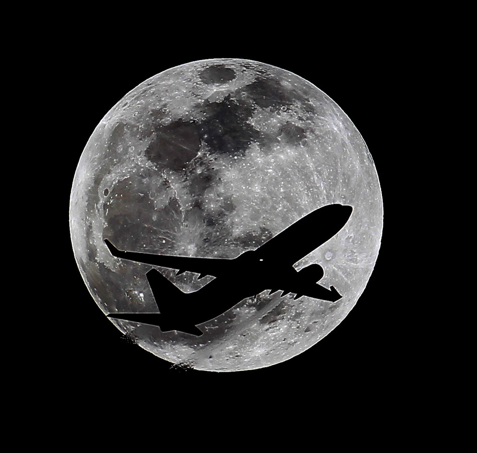 An airliner crosses the moon's path, Monday, April 14, 2014, above Whittier, Calif., approximately one hour before a total lunar eclipse. Then, on April 29, the Southern Hemisphere will be treated to a rare type of solar eclipse. In all, four eclipses will occur this year, two lunar and two solar. (AP Photo/Nick Ut)