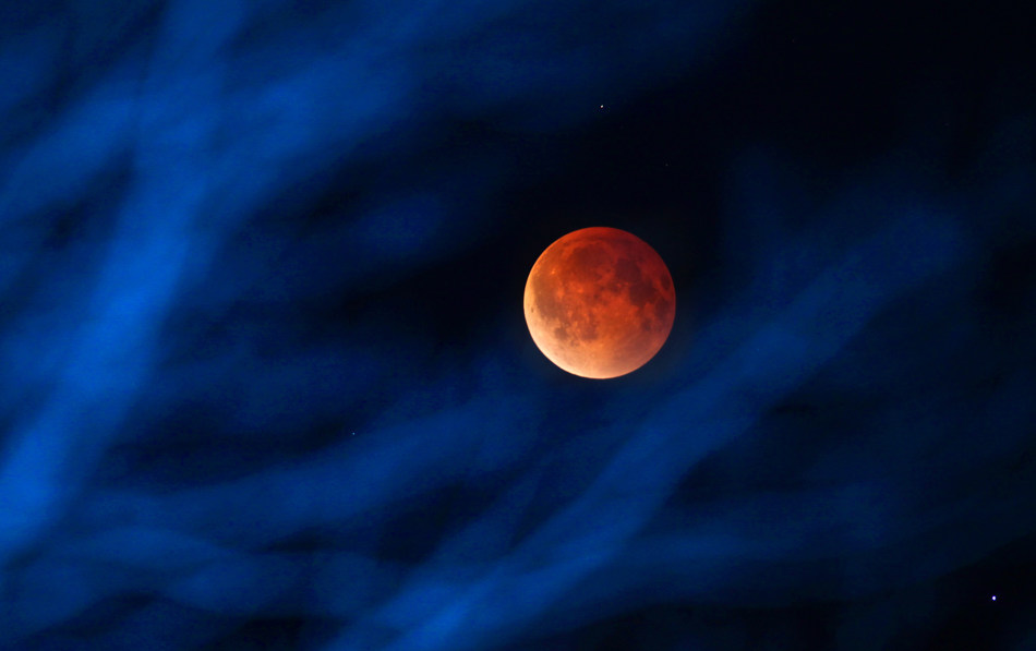 The moon glows a red hue during a total lunar eclipse Tuesday, April 15, 2014, as seen from the Milwaukee area. Tuesday's eclipse is the first of four total lunar eclipses that will take place between 2014 to 2015. (AP Photo/Milwaukee Journal-Sentinel, Mike De Sisti)