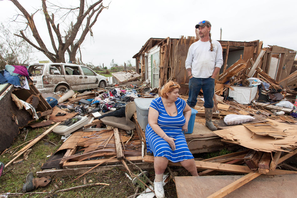 Raella Faulkner, at left, and Bobby McElroy survey what's left of their home Monday, April 28, 2014 after a tornado struck the town of Vilonia, Ark. late Sunday. The couple rode out the storm safely in a nearby storm shelter. Vilonia was hit hard Sunday after a tornado system ripped through several states in the central U.S. and left more than a dozen dead in a violent start to this year's storm season, officials said.  (AP Photo/Karen E. Segrave)