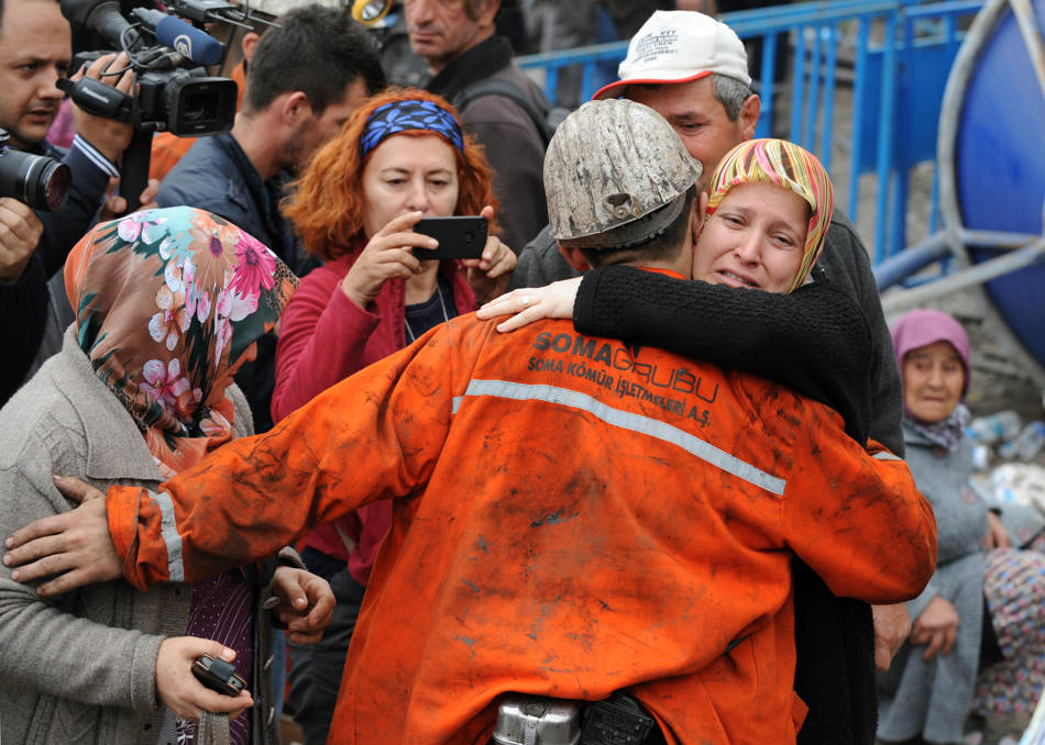 Family members hug a rescued miner outside the coal mine in Soma, Turkey, Wednesday, May 14, 2014.  Rescuers desperately raced against time to reach more than 200 miners still trapped underground Wednesday after an explosion and fire at the coal mine killed at least 238 workers, Erdogan said in Soma.(AP Photo/Depo Photos