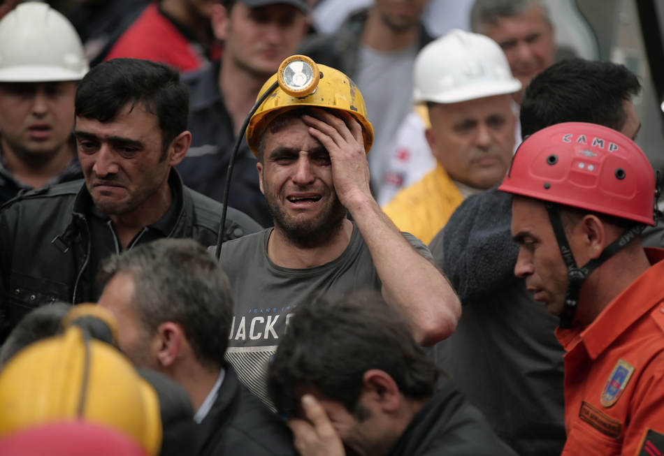 A miner cries as rescue workers carry the dead body of a miner from the mine in Soma, western Turkey, Wednesday, May 14, 2014. An explosion and fire at the coal mine killed at least 232 workers, authorities said, in one of the worst mining disasters in Turkish history. Turkey's Energy Minister Taner Yildiz said 787 people were inside the coal mine at the time of the accident. (AP Photo/Emrah Gurel)
