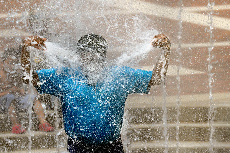 DAVID ZALAZNIK/JOURNAL STAR  Makayla Howard, 11, directs sprays of water to her face in the fountain at the Gateway Building on Peoria's riverfront Sunday, June 1 as she and other family members try to temper the heat of the afternoon.