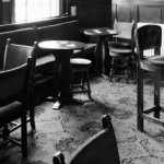 Black and white photograph of pub tables and chairs.