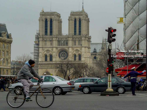 A biker in Paris in front of the Notre Dame Cathedral