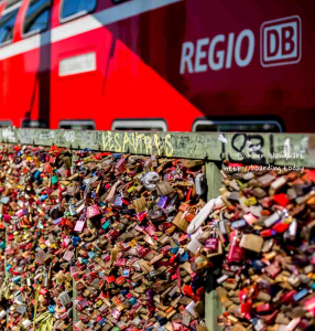 A train passes the Hohenzollern Bridge with its love locks in Cologne, Germany