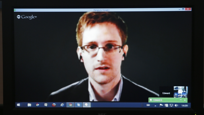 """Edward Snowden is seen on a screen as he speaks via video conference with members of the Committee on Legal Affairs and Human Rights of the Parliamentary Assembly of the Council of Europe during an hearing on """"mass surveillance"""" in Strasbourg, April 8, 2014."""