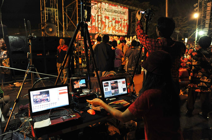 """An unidentified video editor operates an editing system during a large red-shirt rally on the Royal Plaza on Jan 29, 2013 in Bangkok, Thailand."" [Shutterstock]"