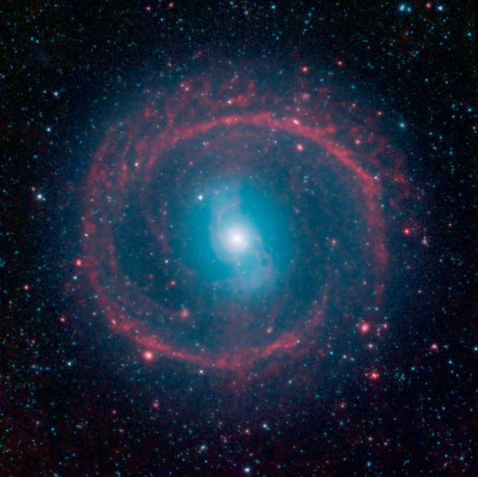 "It might look like as spoked wheel or even a ""Chakram"" circular weapon wielded by television's fictional warrior Xena, but this ringed galaxy is actually a vast place of stellar life. A newly released image from NASA's Spitzer Space Telescope shows the galaxy NGC 1291. Though the galaxy is quite old, roughly 12 billion years, it is marked by an unusual ring where newborn stars are still bursting to life."
