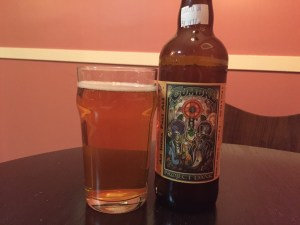 22oz bottle of La Cumbre Project Dank IPA poured into a nonic pint glass.