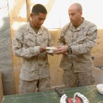 In keeping with tradition, the oldest and youngest Marines present are given the first piece of the Marine Corps birthday cake.  Here, 1st Sgt. Eric W. Rummel (right) of Company F, TF 2/7, hands the first piece of cake to one of his riflemen, Lance Cpl. Luis Rocha.  Fox Company Marines celebrated the Marine Corps birthday at Forward Operating Base Now Zad, Nov. 10. (Marine Corps photo by Sgt. Freddy G. Cantu, Combat Camera, TF 2/7)