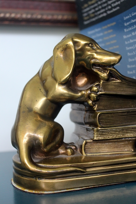 brass dachshund eating book